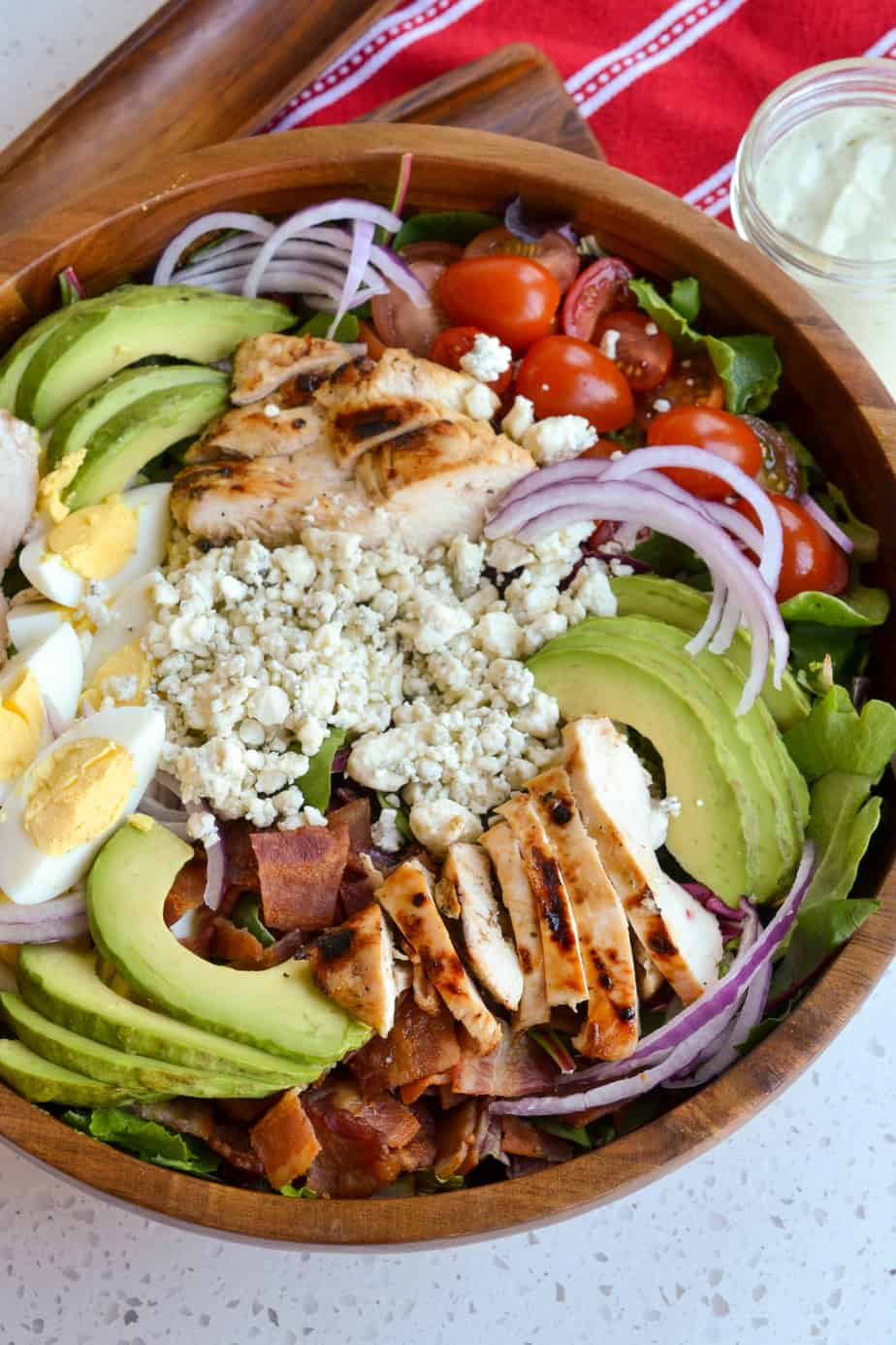 A salad bowl filled with greens, chicken, bacon, tomatoes, eggs, and avocado.