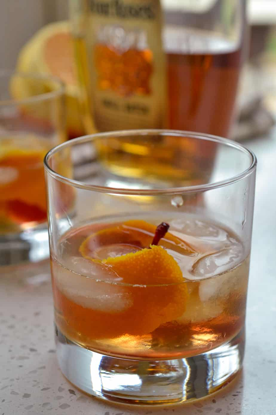 Old fashioned bourbon whiskey cocktail with orange twist and maraschino cherry.