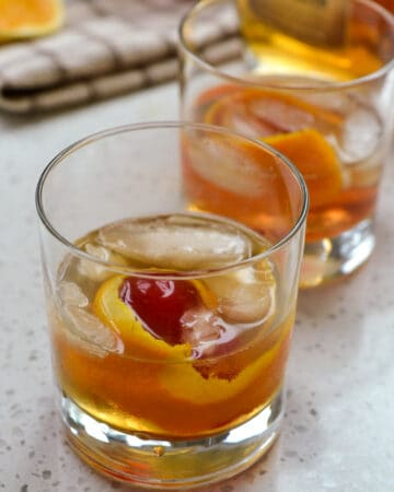 Old fashioned cocktail with orange twist and maraschino cherry