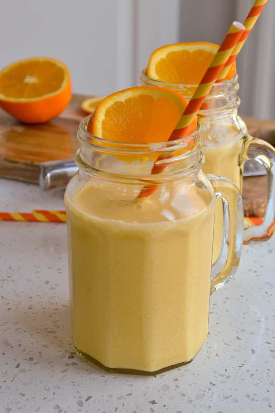 Homemade orange julius in glasses with orange slices and straws