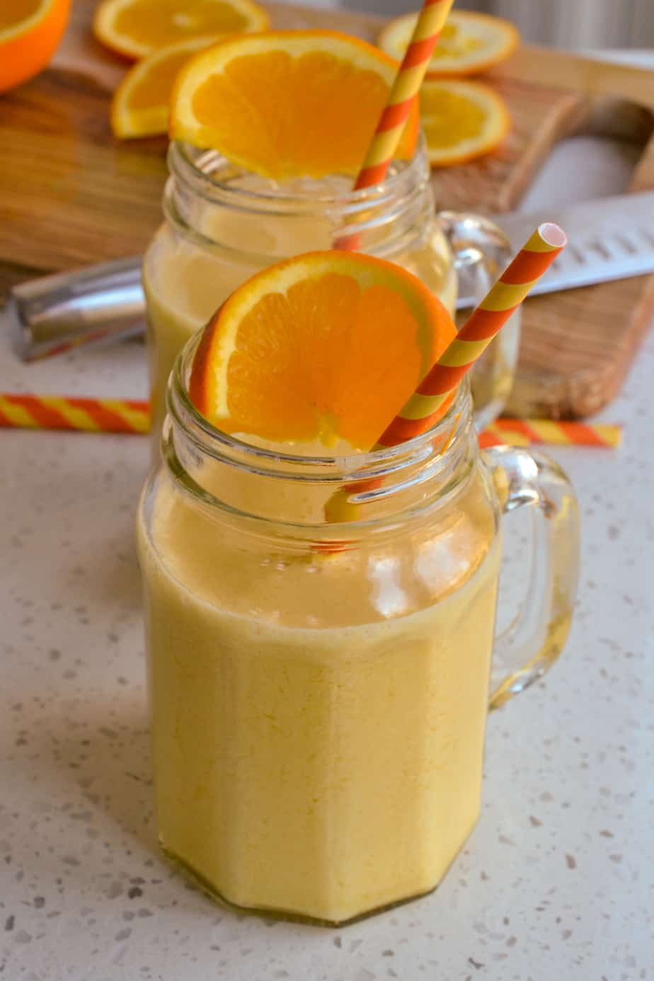 Glasses of creamy orange julius topped with orange slices