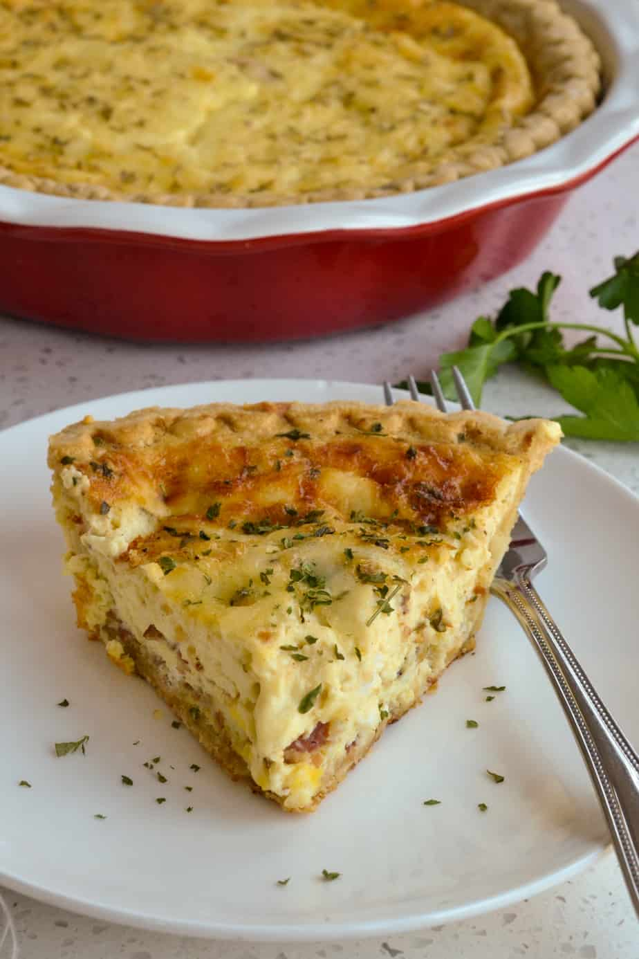 A piece of cheesy Quiche Lorraine on a plate.