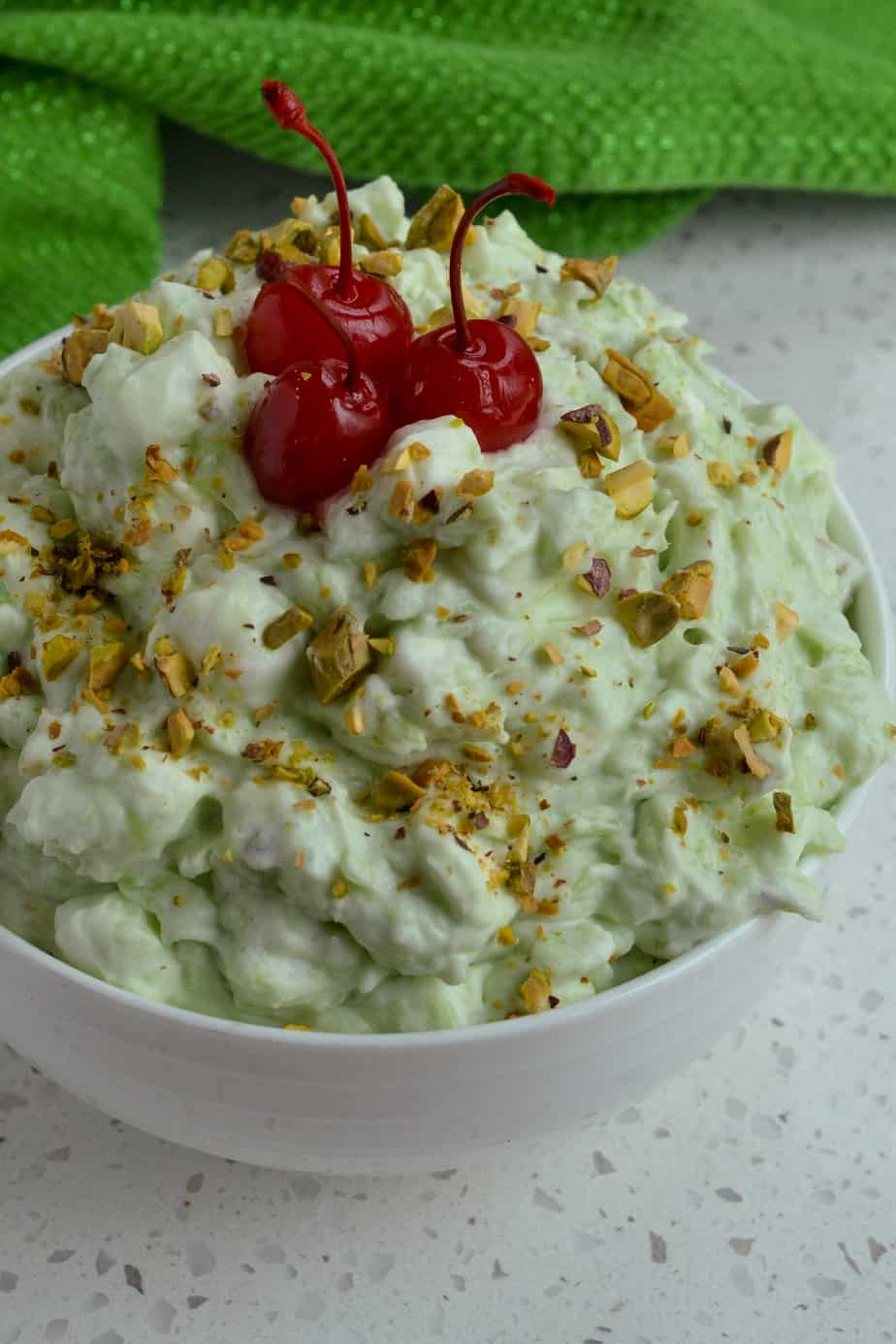 Watergate Salad garnished with pistachio nuts and cherries.