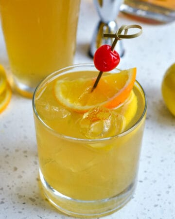 Whiskey Sour with orange and cherry garnish