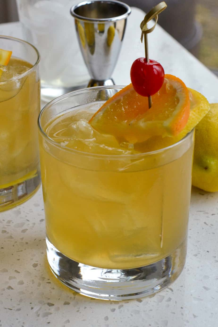 Whiskey sour cocktail garnished with an orange slice, lemon slice, and cherry.