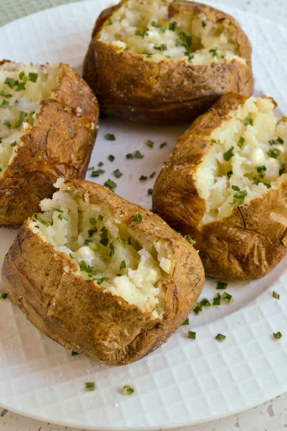 Baked potatoes with fresh creamy butter and chives.