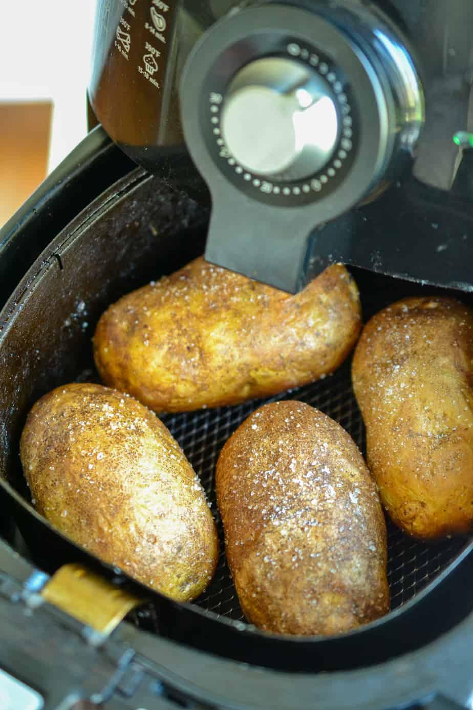 Four potatoes in an air fryer.
