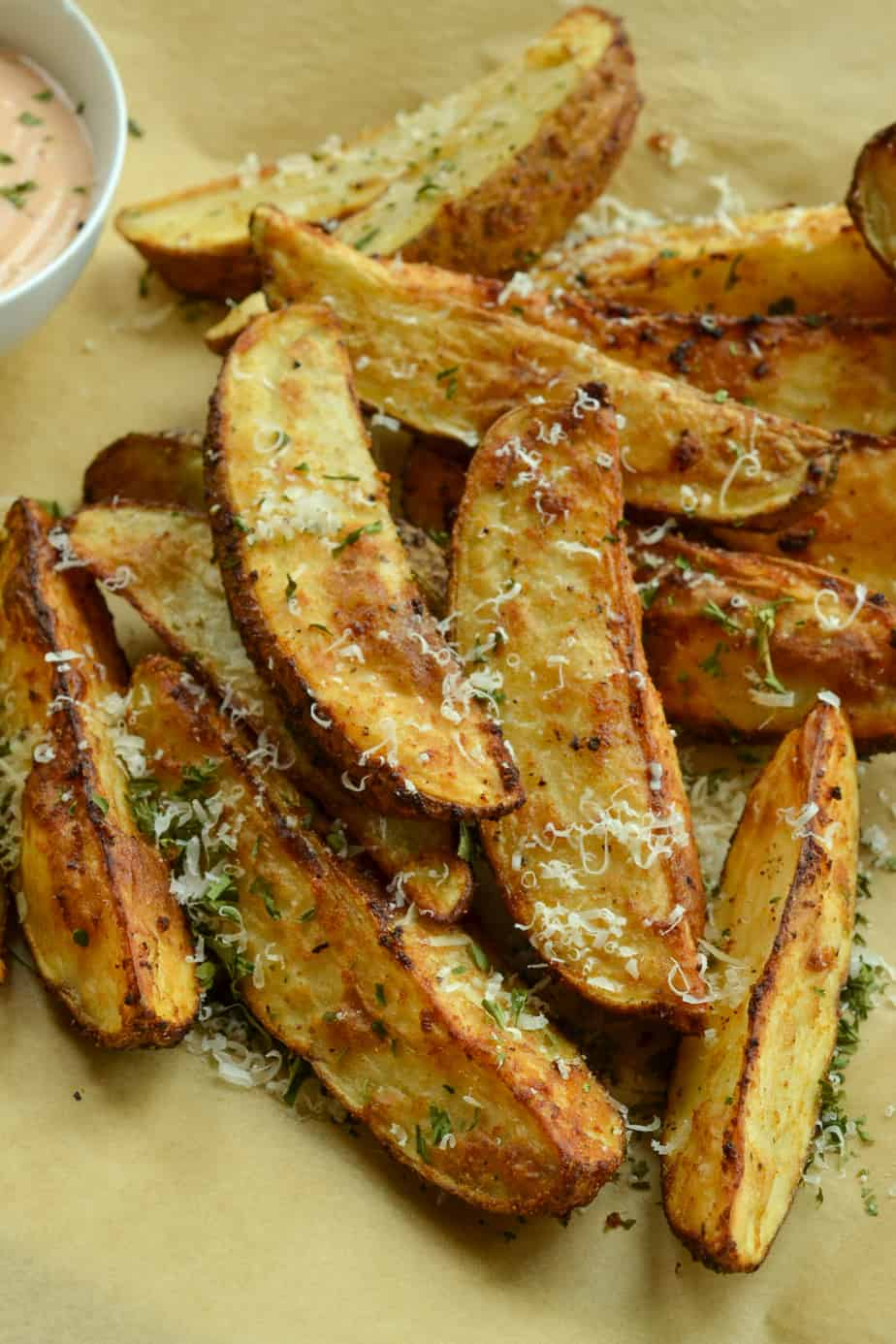 Crispy air fried potato wedges sprinkled with Parmesan cheese and parsley