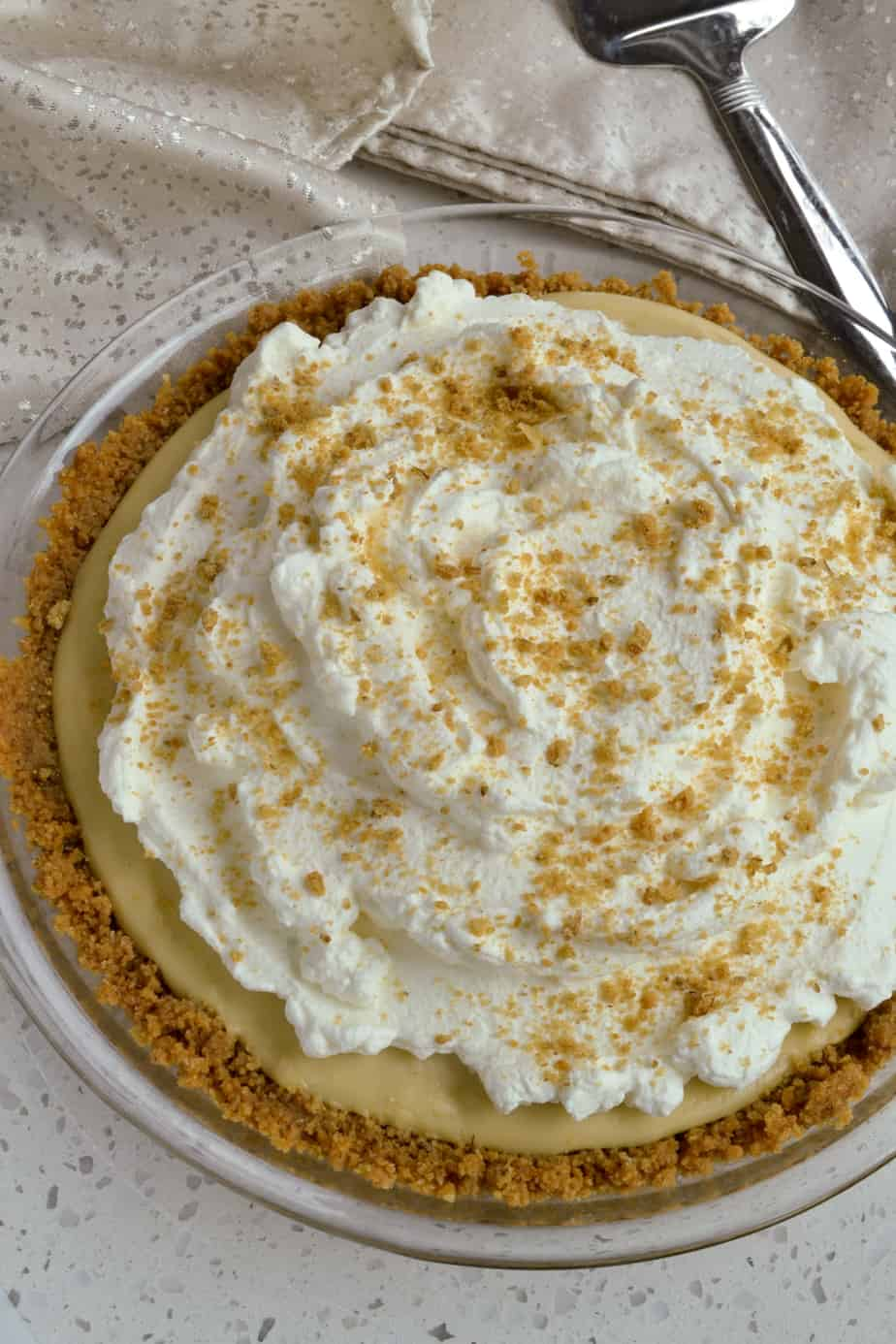 A whole butterscotch pie topped with whipped cream.