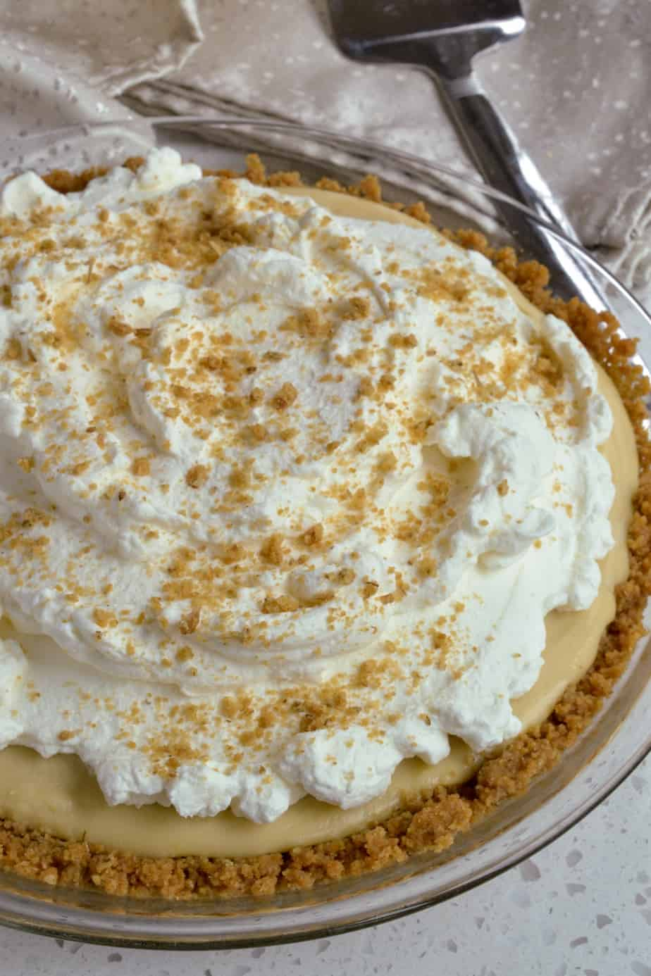 A creamy butterscotch pie topped with whipped cream and crushed breakfast biscuits