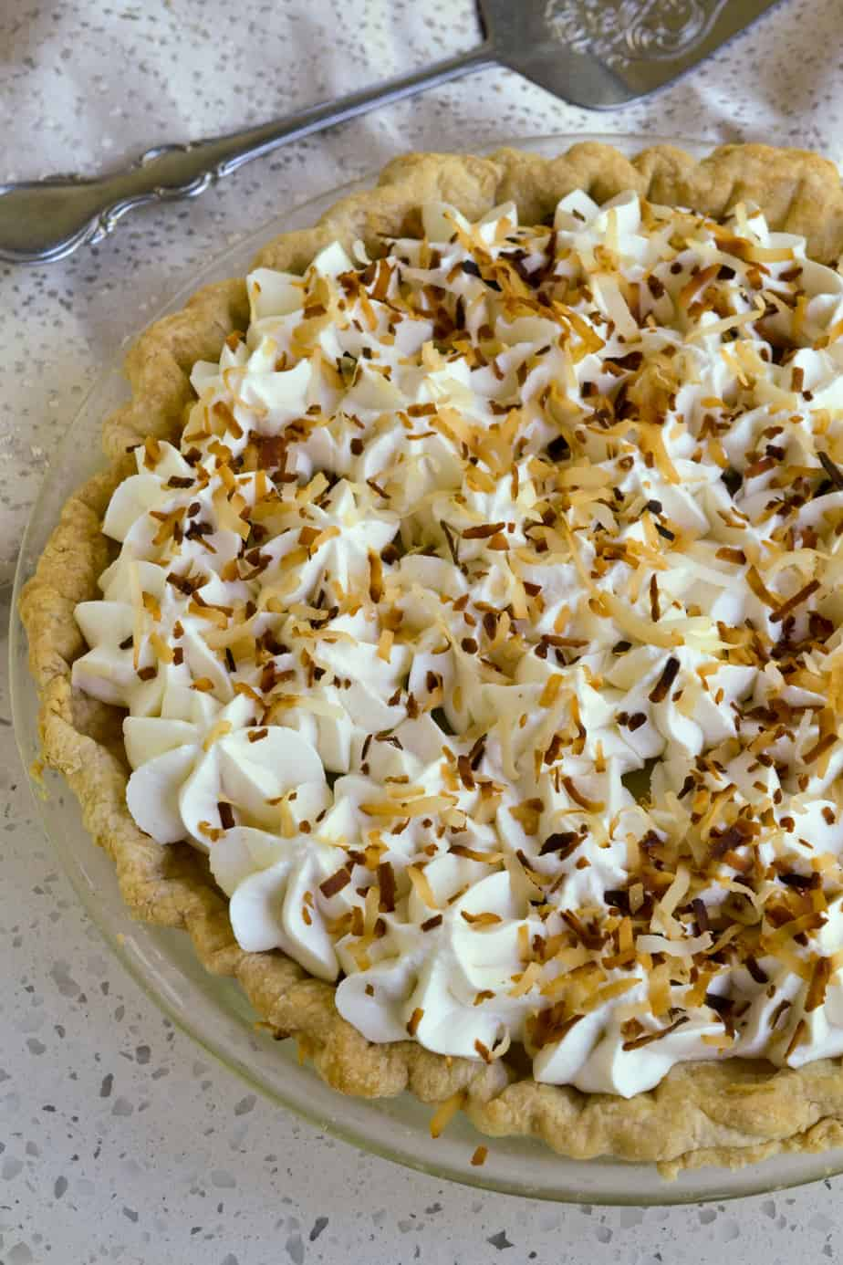 The top of this classic cream pie is topped with whipped cream and toasted coconut.
