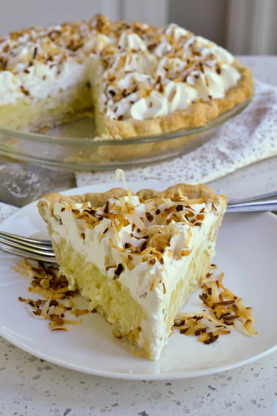 A delicious slice of cream pie with coconut pudding, whipped cream, and toasted coconut.
