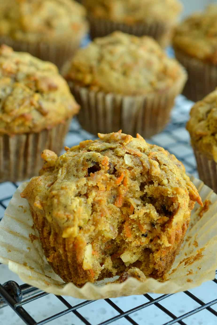 Fresh baked muffins filled with carrots, raisins, coconuts, and apples.