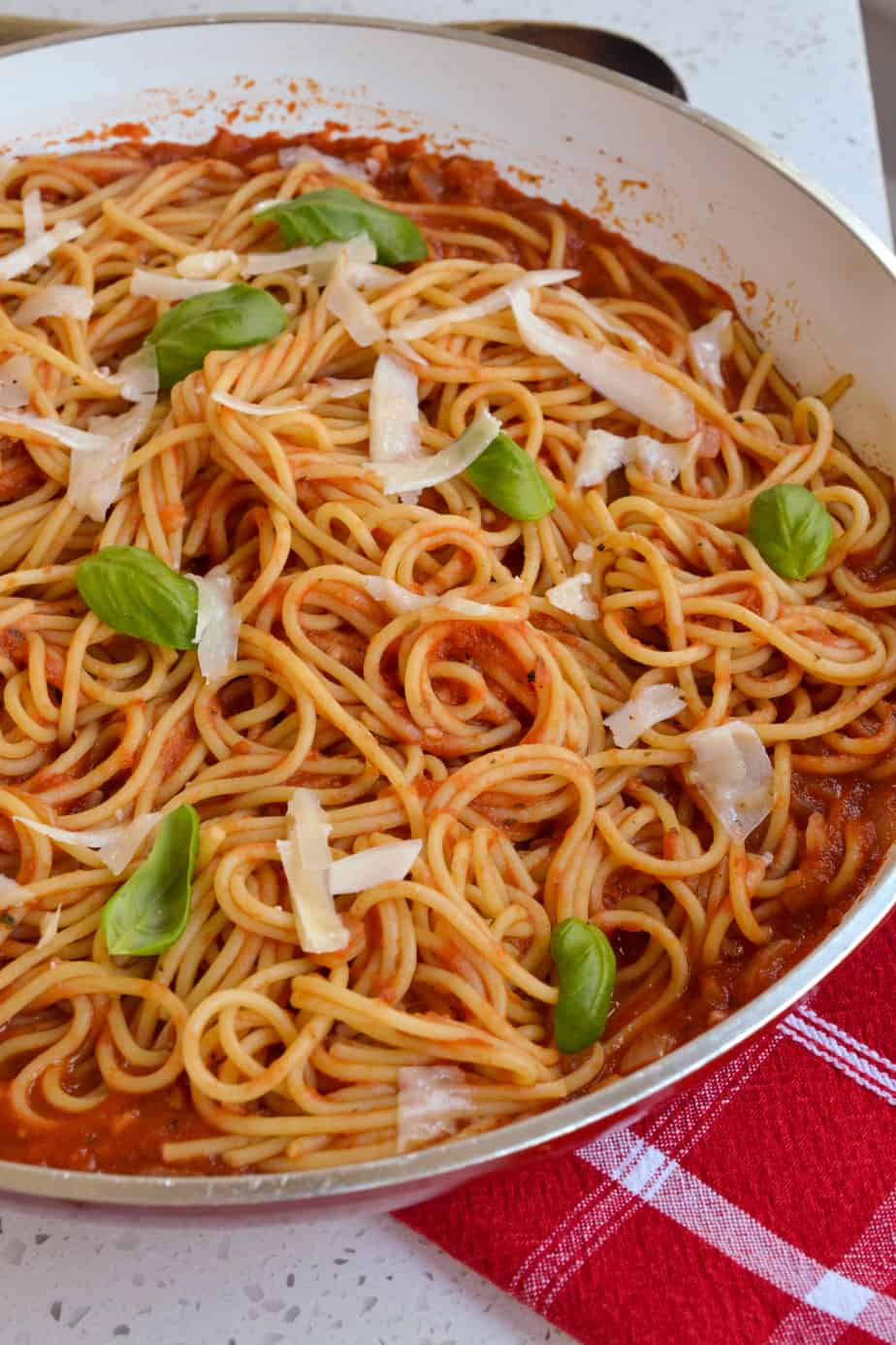 A skillet of spaghetti with tomato sauce.