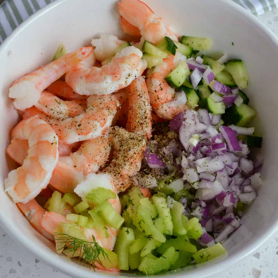 Cooked shrimp, chopped celery, chopped cucumber and chopped red onion in a bowl.