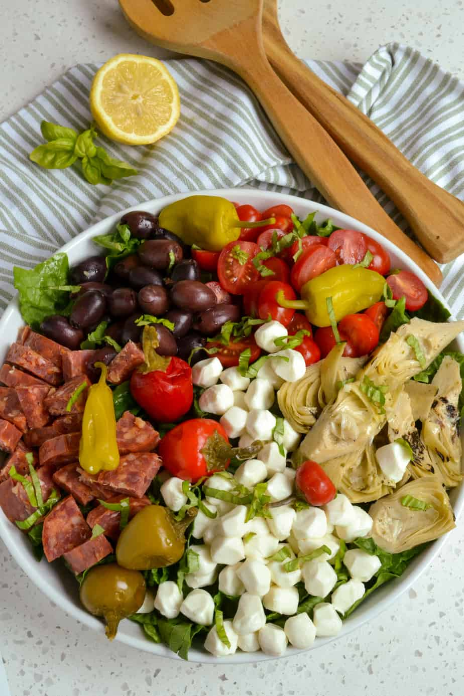 An overhead view of a bowl of antipasto salad with salami, mozzarella, tomatoes, and olives.