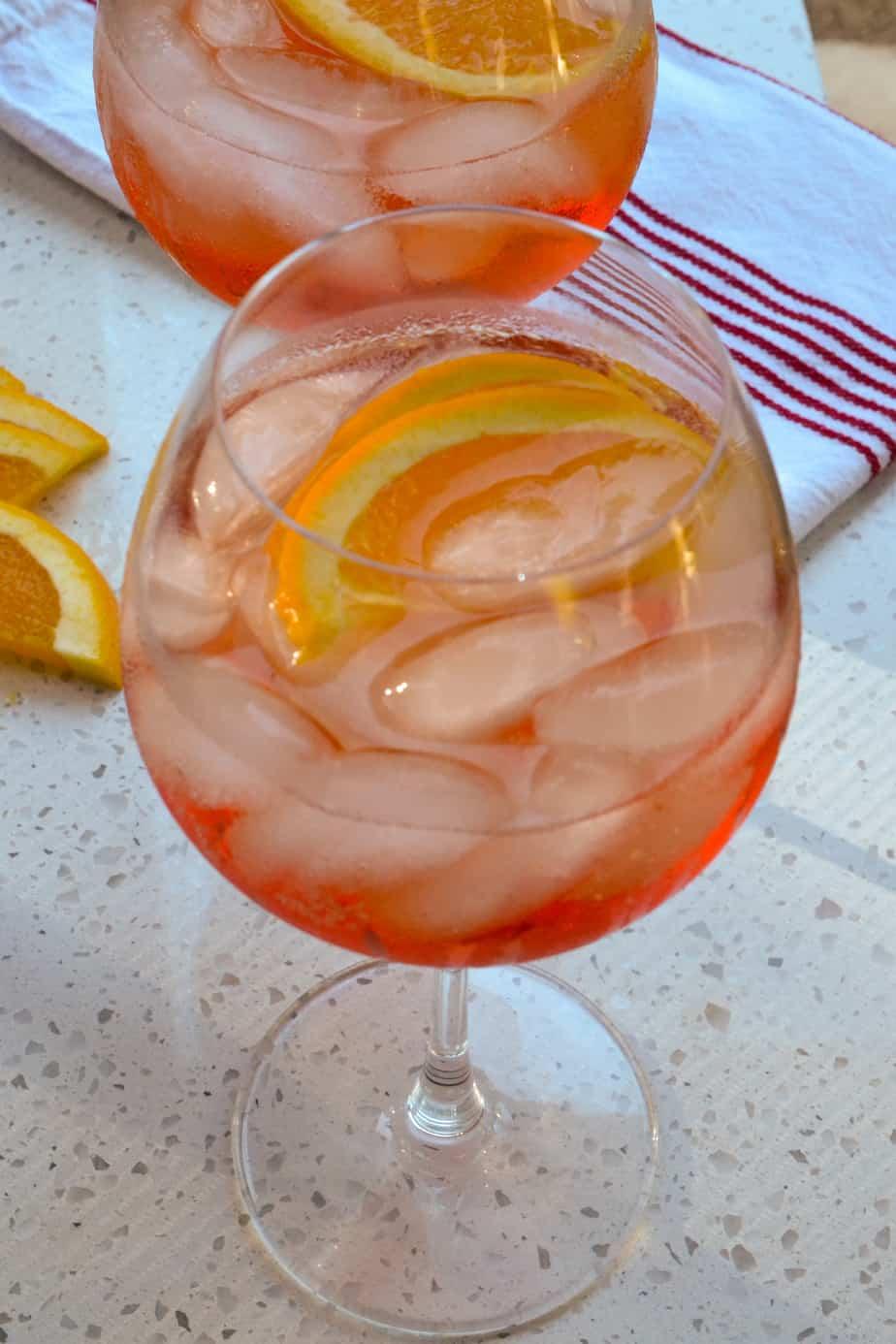 Aperol spritz cocktail over ice with orange slices.