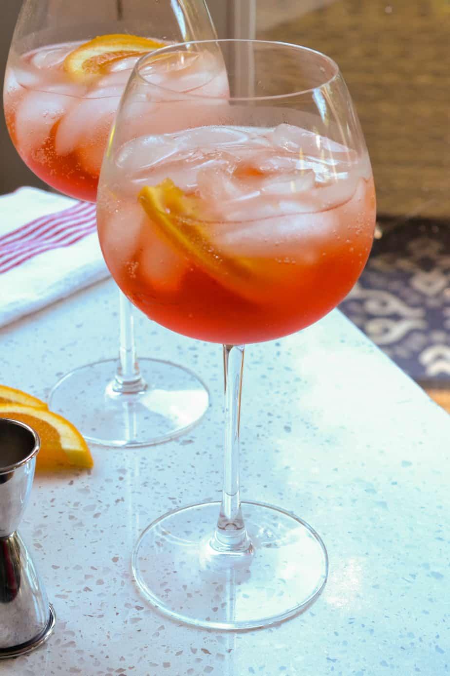 Aperol spritz in big bowl wine glasses with orange slices.