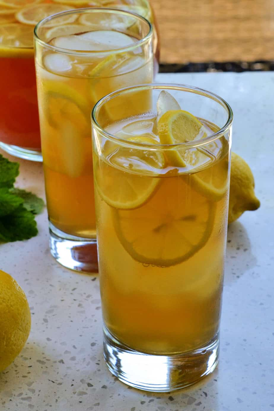 Two ice cold glasses of Arnold Palmer Tea with fresh lemon slices.