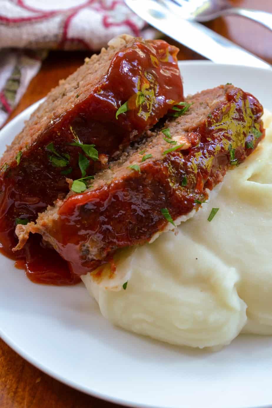 Sliced meatloaf on top of mashed potatoes.