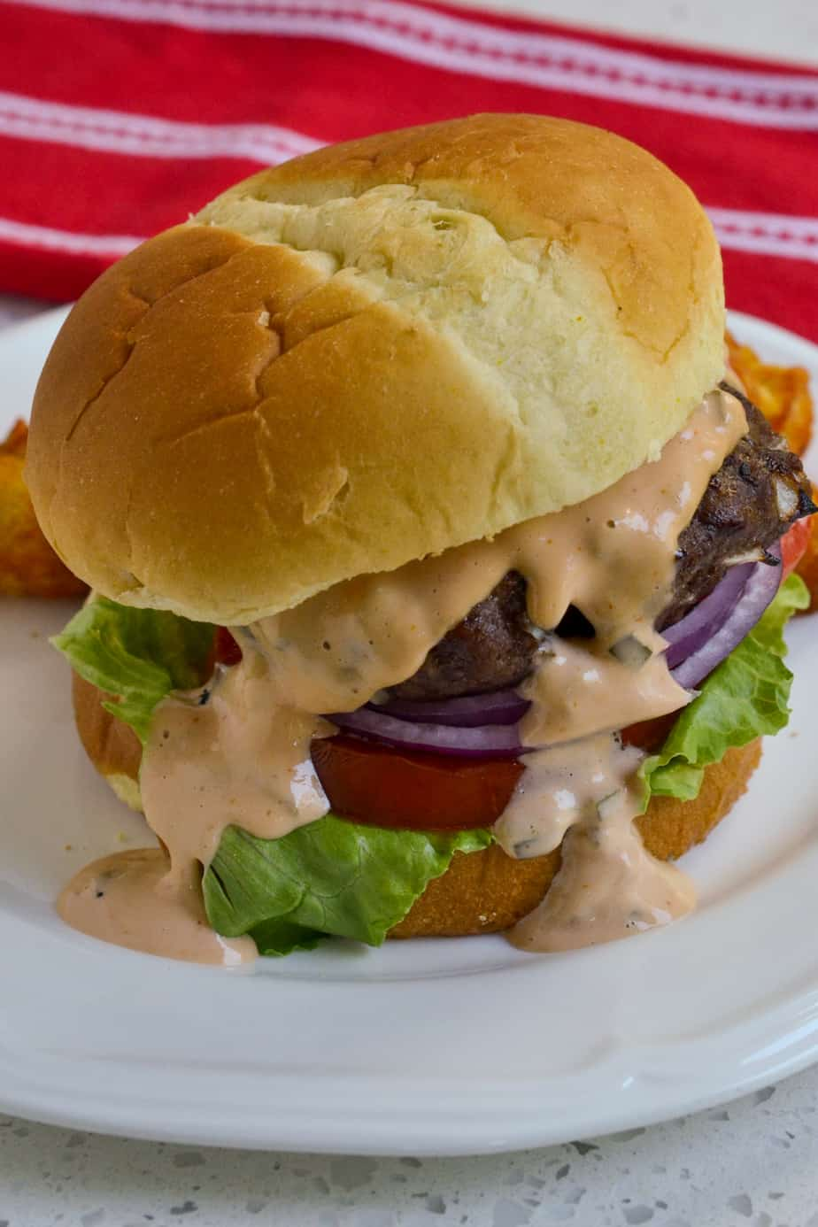 A grilled burger with burger sauce.