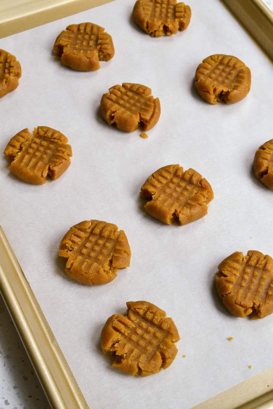 Peanut butter cookie dough prepped on a baking sheet.