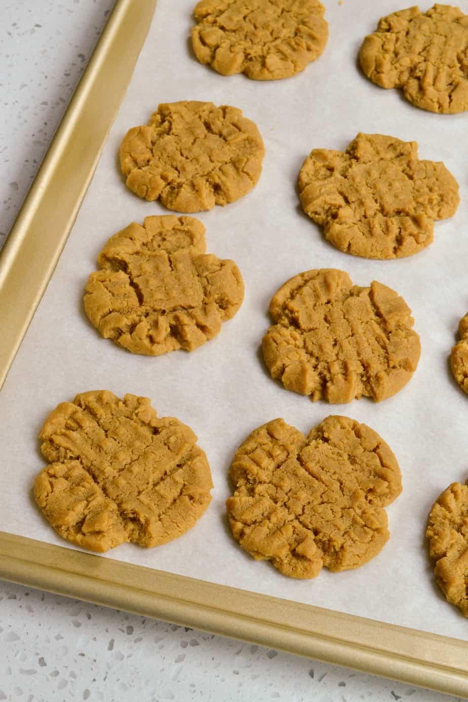 Baked flourless peanut butter cookies on a baking sheet.