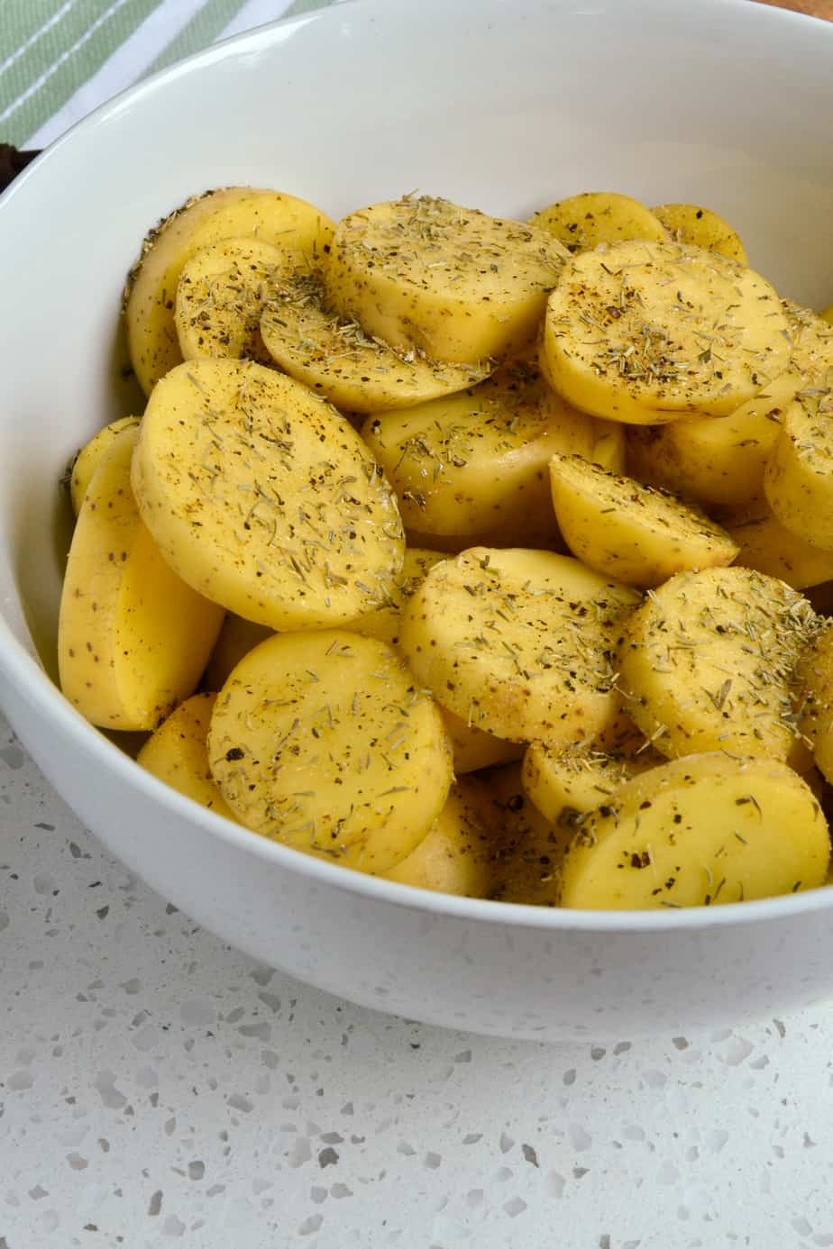 Raw Yukon Gold Potatoes mixed with oil and dried herbs