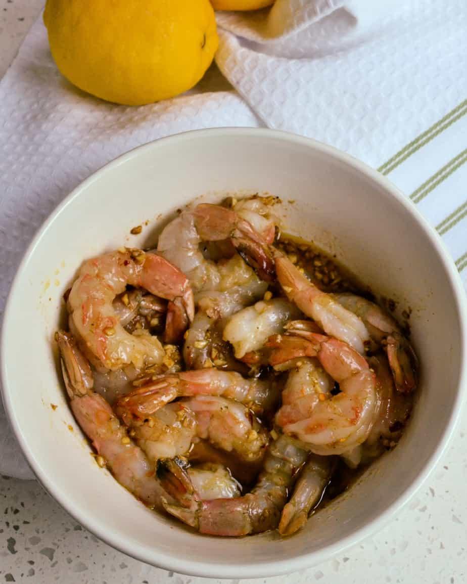Shrimp marinating in a bowl.