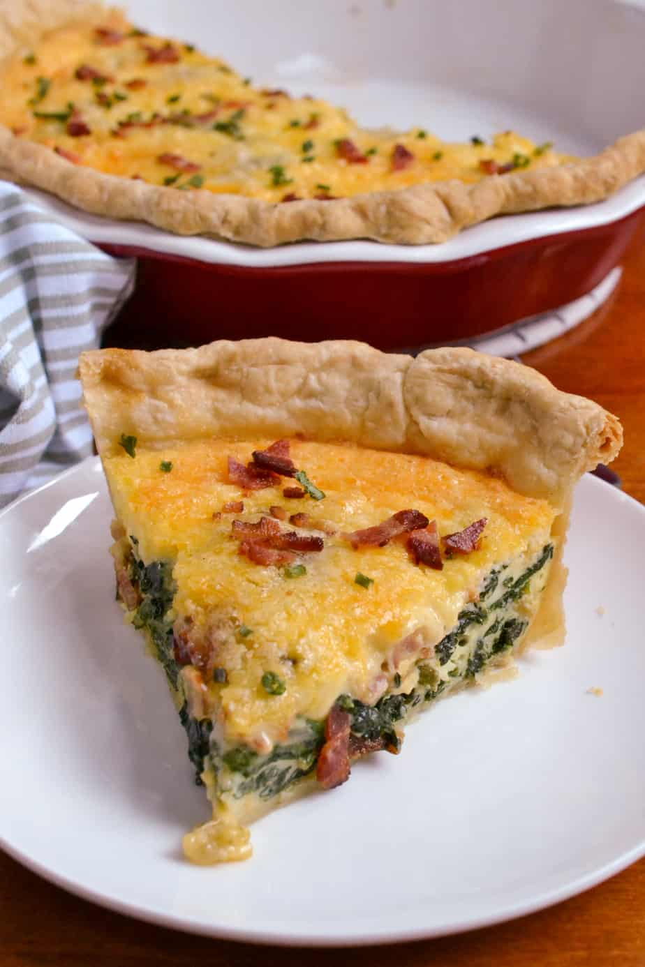 A slice of deep-dish homemade spinach bacon quiche.