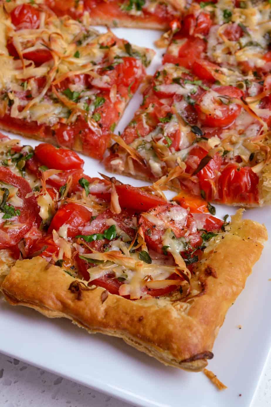 Fresh tomato tart appetizer slices on a platter.