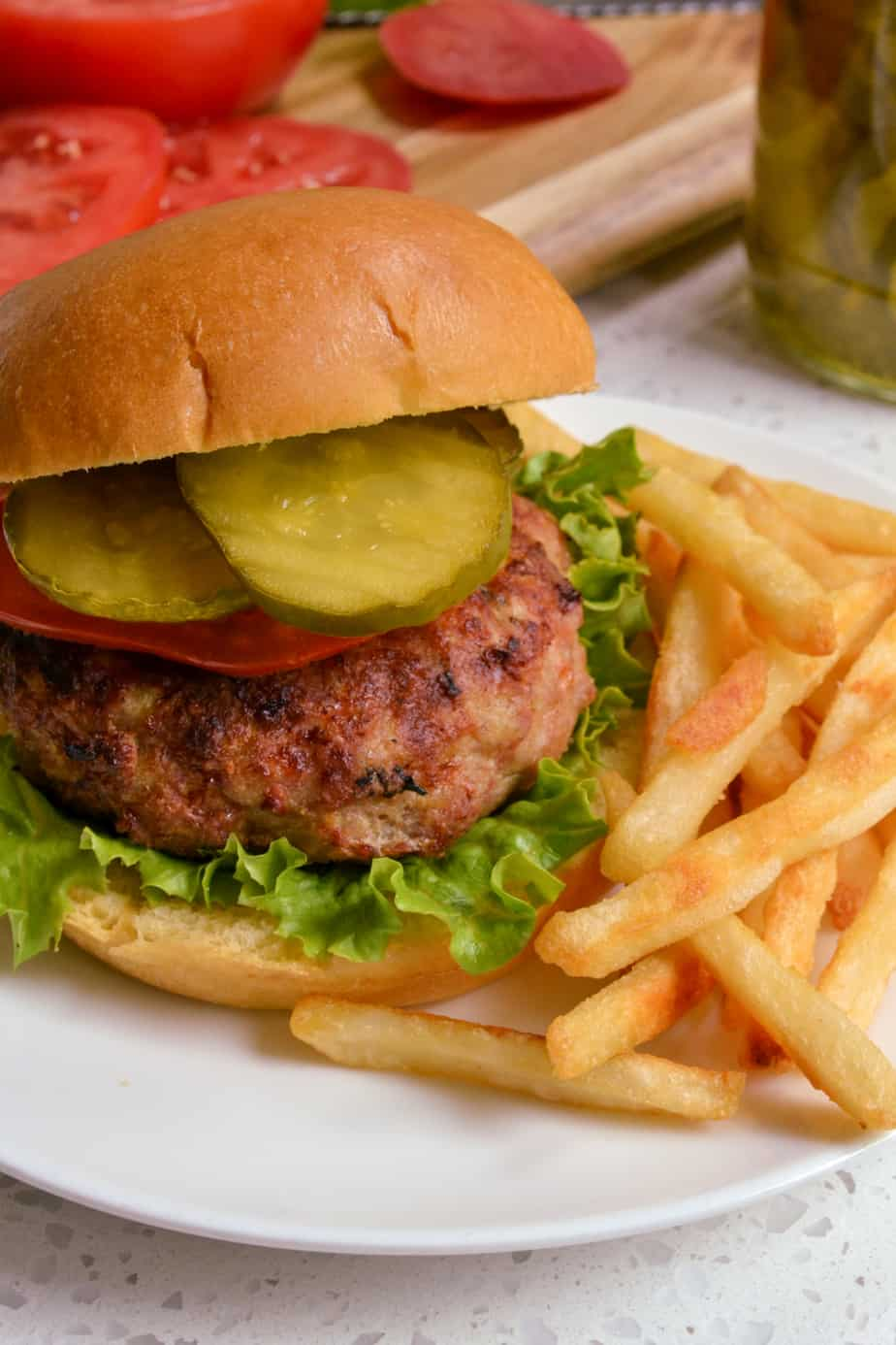 Turkey burger with lettuce, tomato, and pickles.