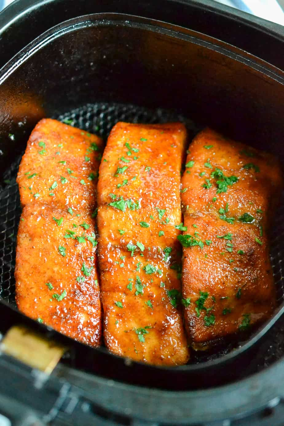 Salmon filets cooked in an air fryer.