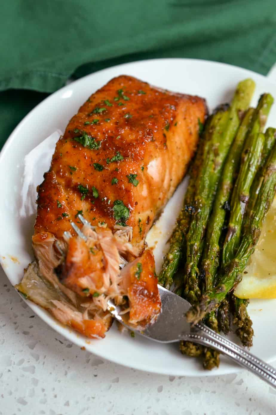 A cooked salmon filet flaked with a fork.