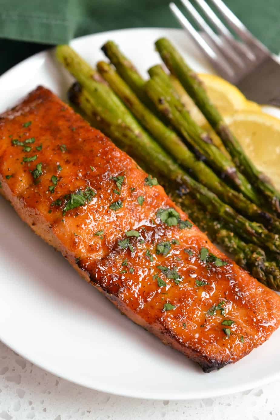 A salmon filet with asparagus on a plate.