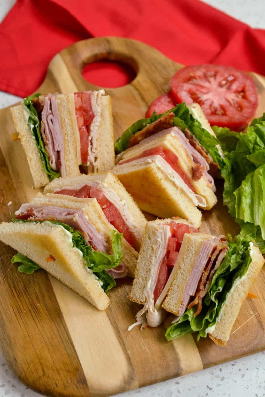 A classic club sandwich quartered on a cutting board.