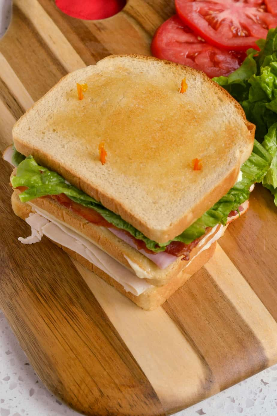Classic whole club sandwich with lettuce, tomato, turkey, ham, and bacon.