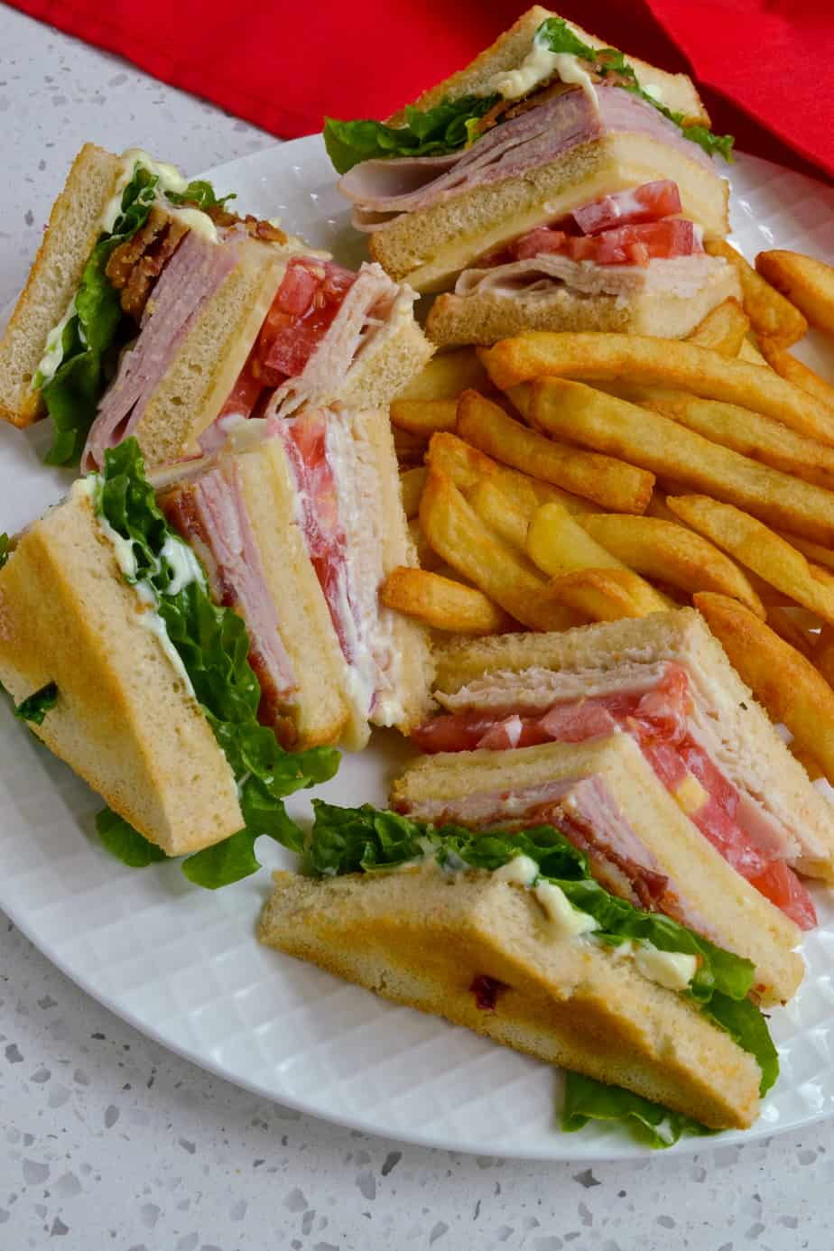 A classic club sandwich served with French fries.