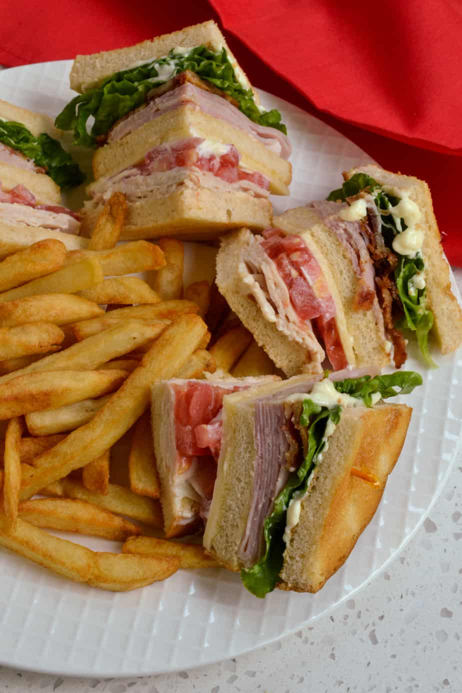 Quartered Club Sandwich served with French fries.