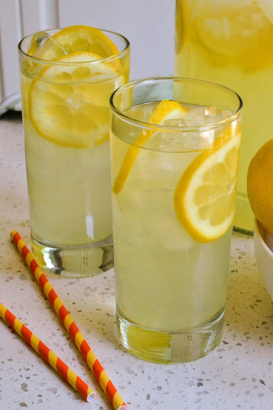 Glasses filled with lemon slices, ice, and fresh lemonade.