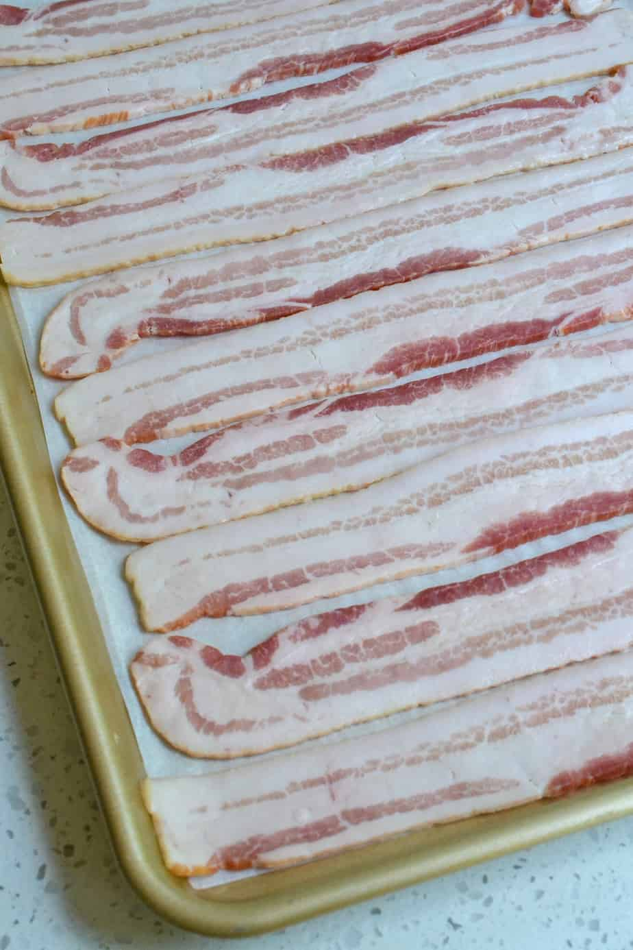 Raw bacon in a single layer on a baking sheet.
