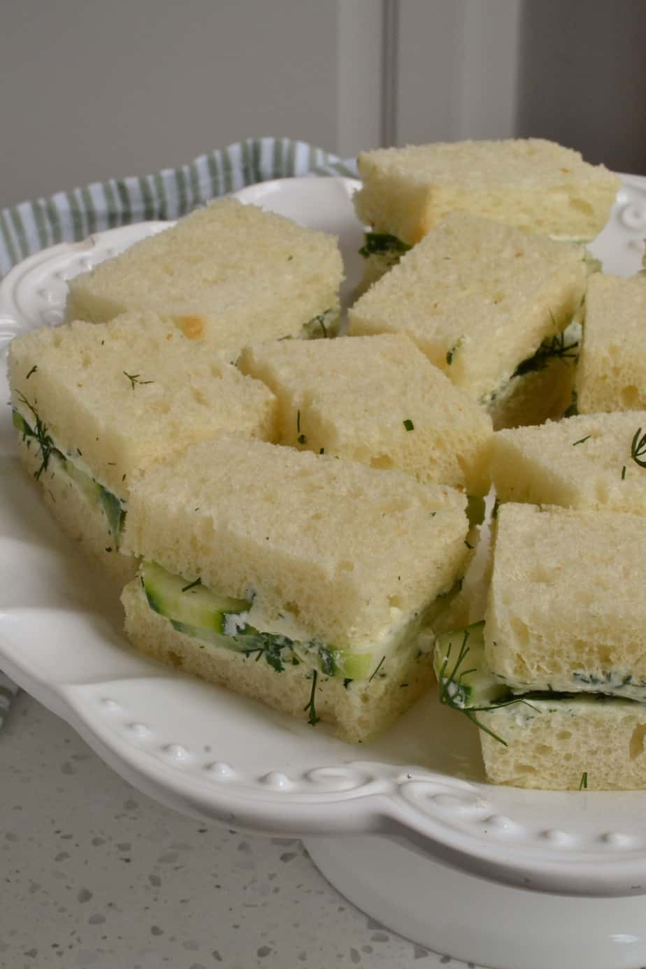 A white party platter with cucumber cream cheese sandwiches.