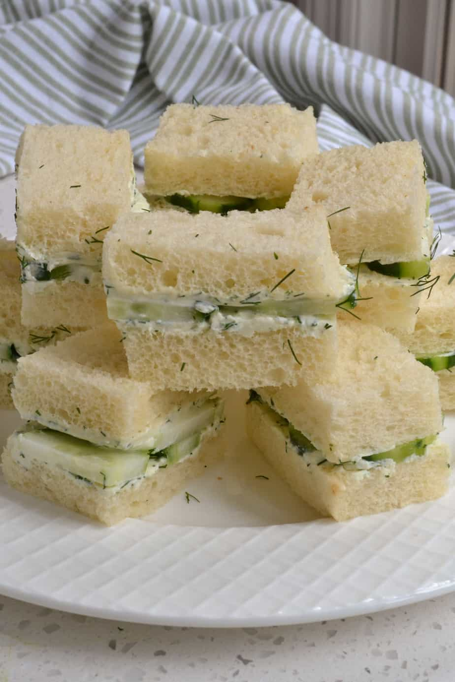 Cucumber tea sandwiches stacked on a plate.