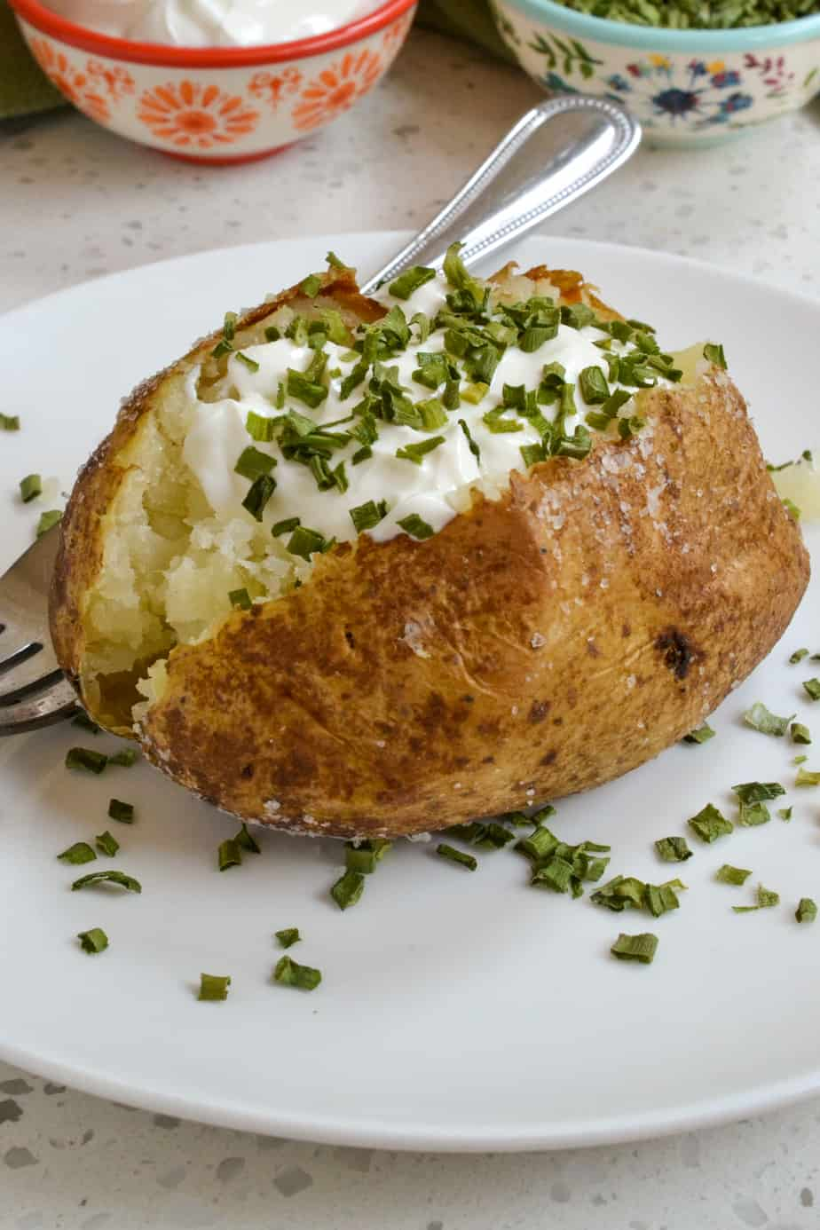 An oven baked potato with sour cream and chives.