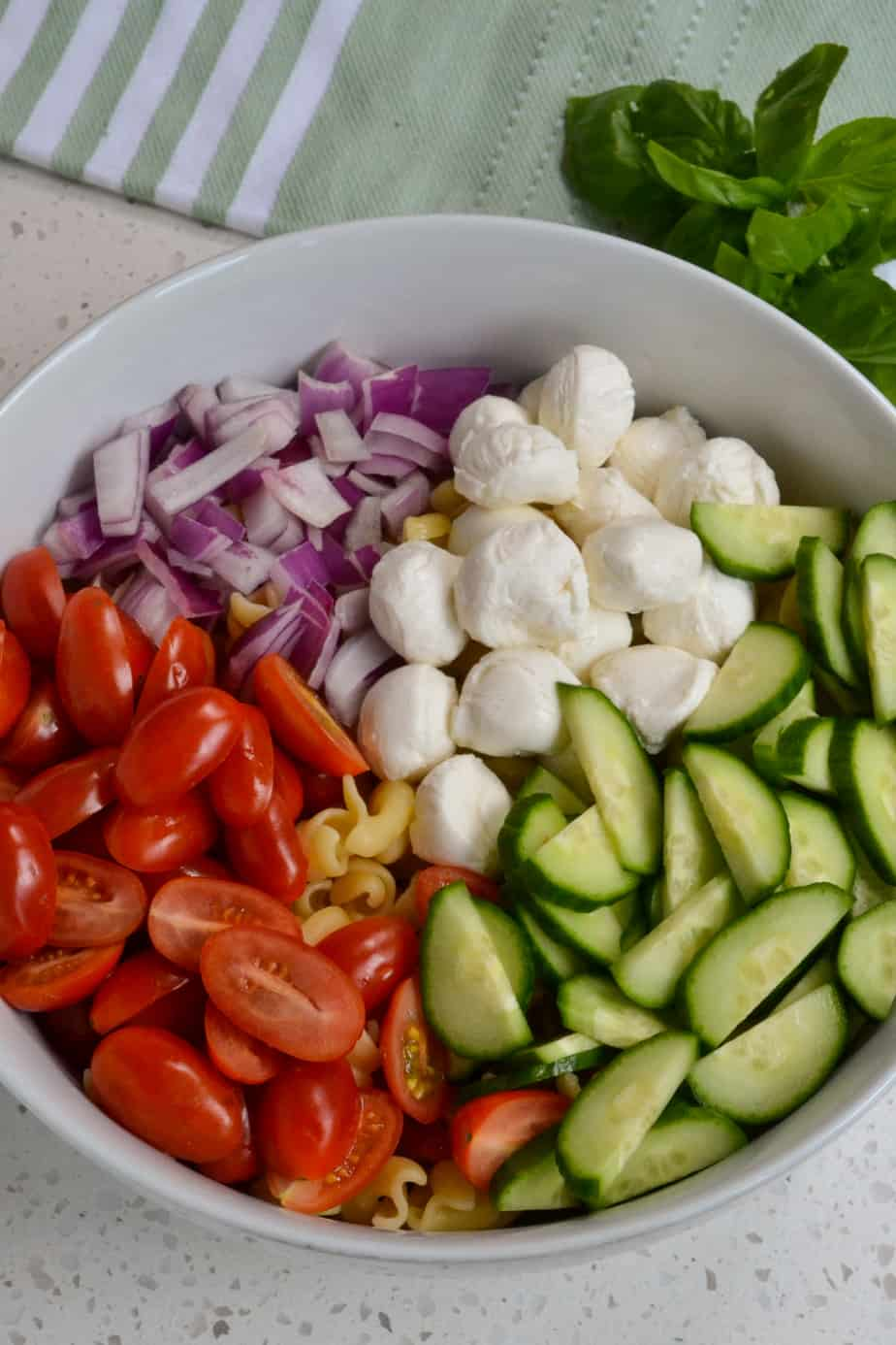 Some of the ingredients for the pasta salad in a bowl.