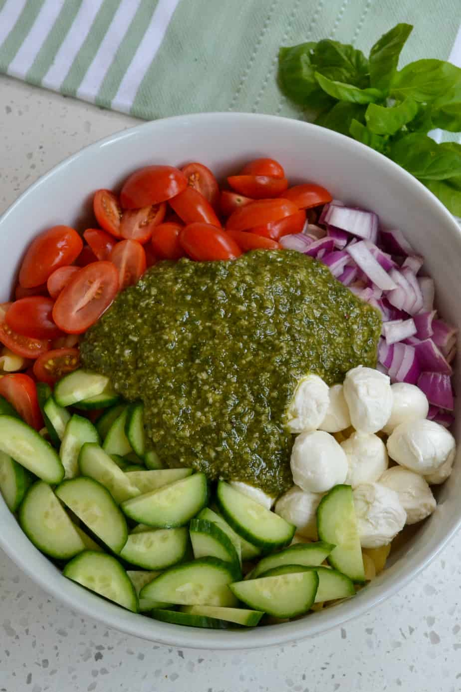 All of the ingredients for the Pesto Pasta Salad in a bowl.