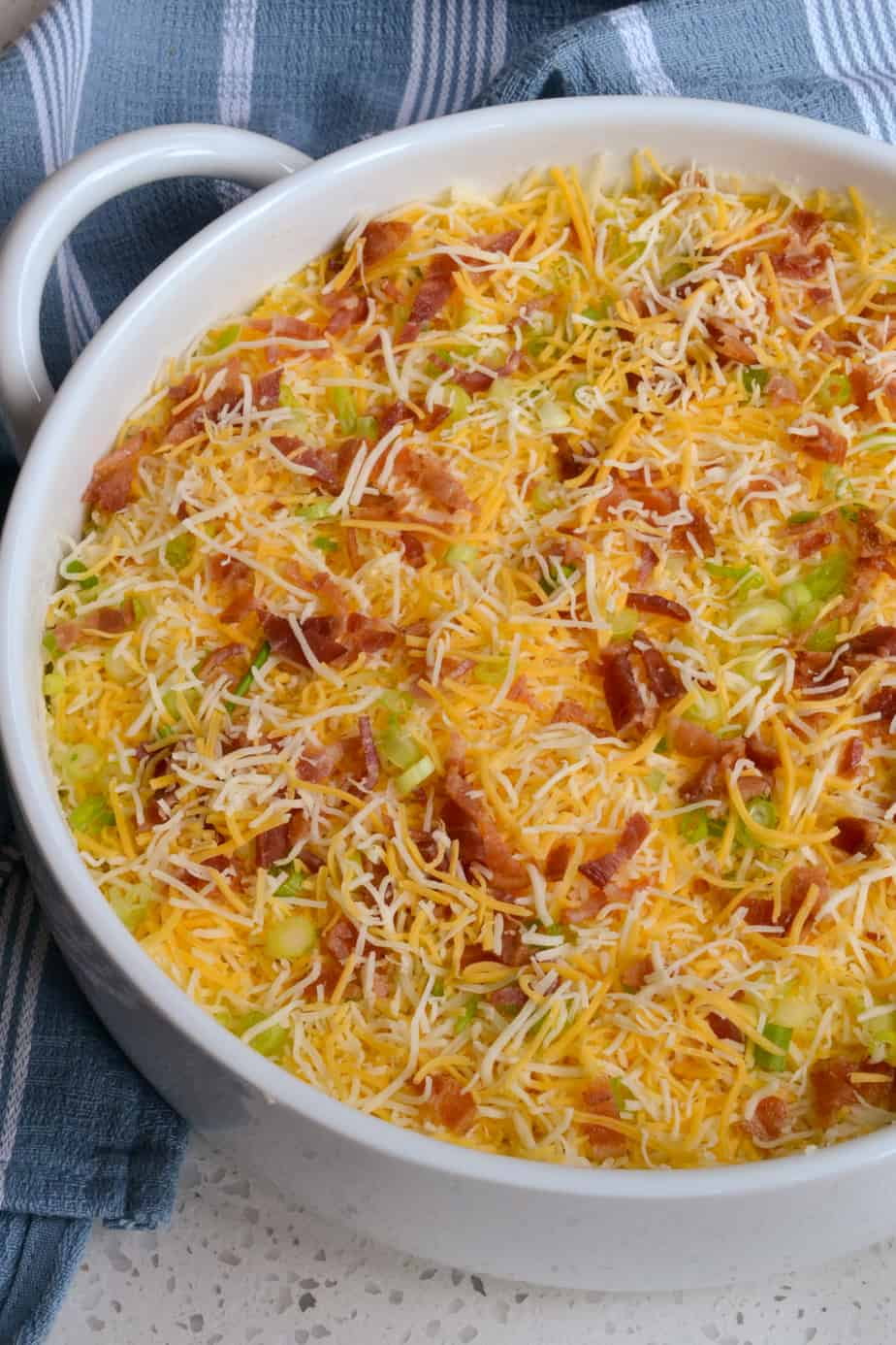 Top the twice baked potatoes with bacon, cheese, and green onions.