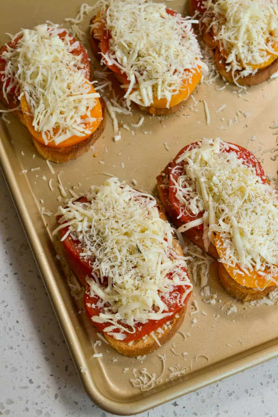 Top the tomato sandwiches with shredded mozzarella and parmesan.