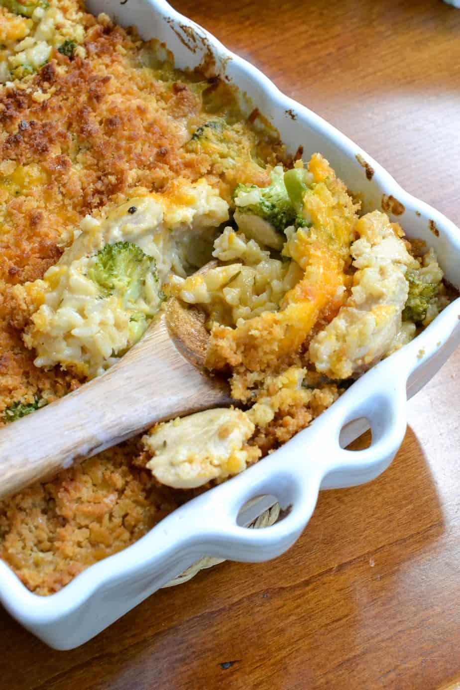 A spoon full of cheesy chicken broccoli rice casserole.