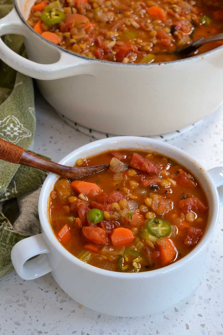 A bowl full of lentil vegetable soup topped with jalapeno rings.